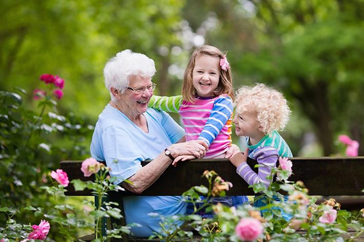 Oma sitzt mit Kindern im Garten auf Bank