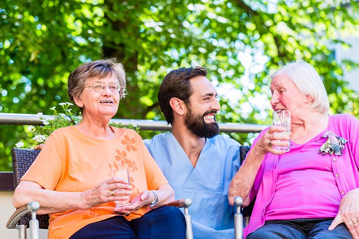Krankenpfleger mit zwei Seniorinnen