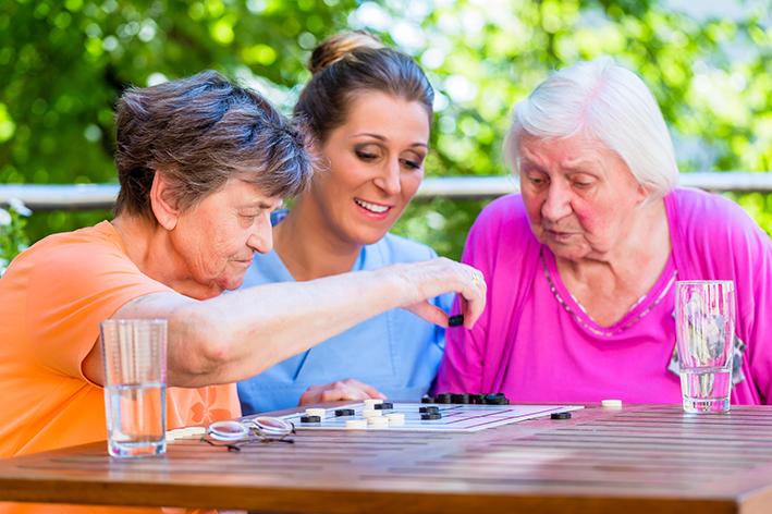 Zwei Senioren spielen mit einer Pflegekraft Mühle