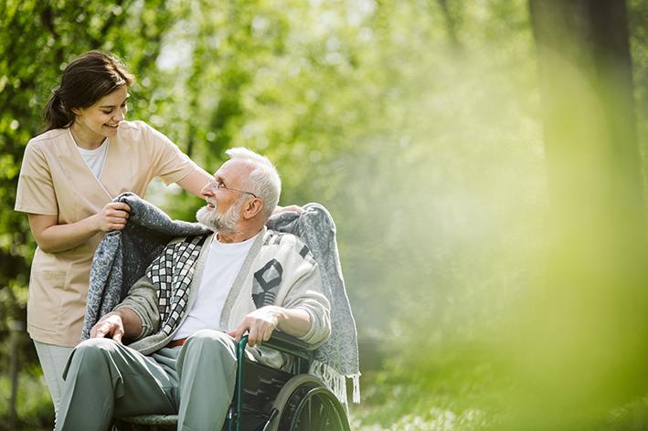 Krankenschwester mit Senior im Rollstuhl im Park