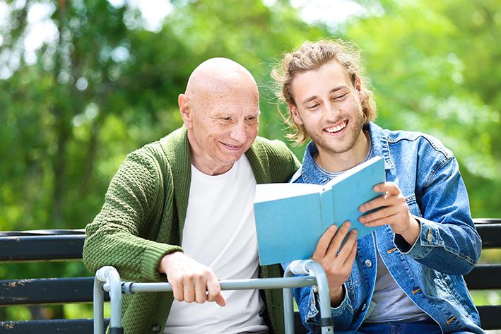 Junger Mann liest Senior aus Buch vor