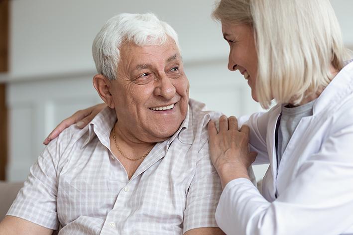Älterer Herr und Krankenschwester im Gespräch