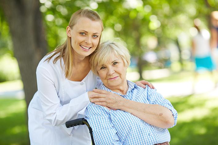 Pflegerin und ältere Dame im Rollstuhl