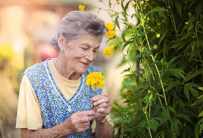 Ältere Dame mit gelber Blume