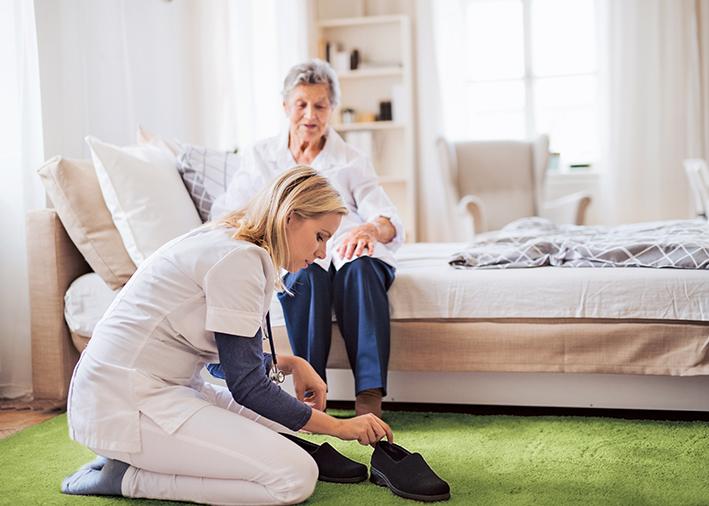Krankenschwester hilft beim Schuhe anziehen