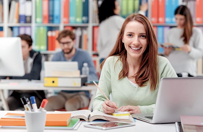 Studentin mit Buch, Notizzettel, Stift und Laptop