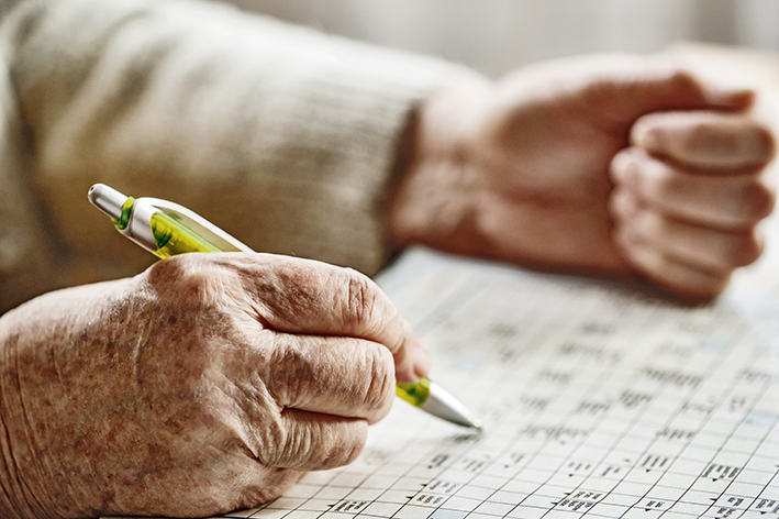 Seniorin löst ein Kreuzworträtsel, Sudoku