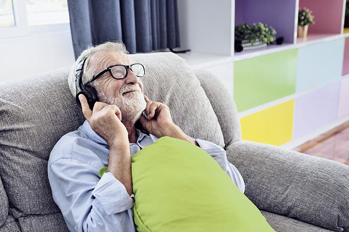 Senior hört Musik über Kopfhörer