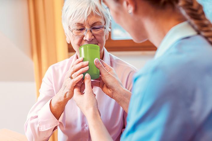 Krankenschwester reicht Dame einen Becher zu trinken