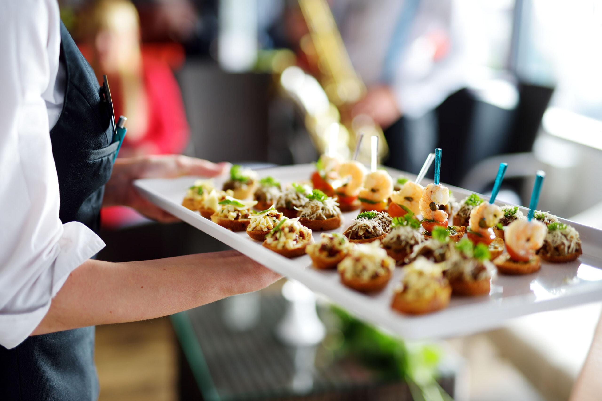 Kellner trägt Teller mit Fleischgericht