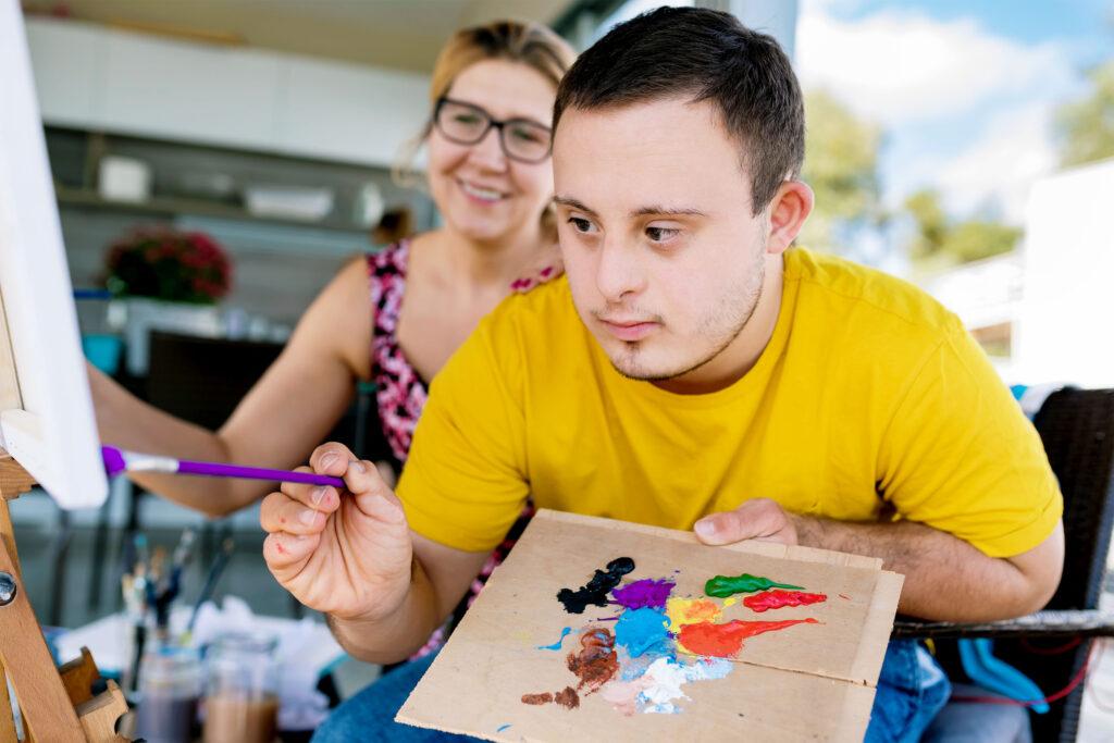 Junge mit Down-Syndrom malt