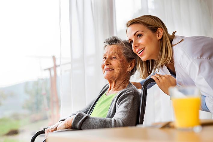 Krankenschwester schaut Dame im Rollstuhl über die Schulter